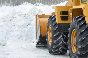 The bulldozer cleans the road after a blizzard